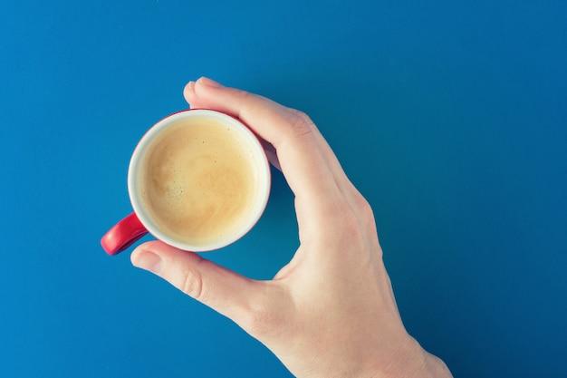 Feminino mão segura um copo vermelho de café sobre um fundo azul Foto Premium