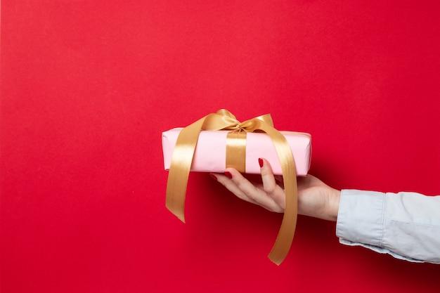 Feminino mão segura um embrulho embrulhado em papel rosa e um laço de fita de ouro vermelho Foto Premium