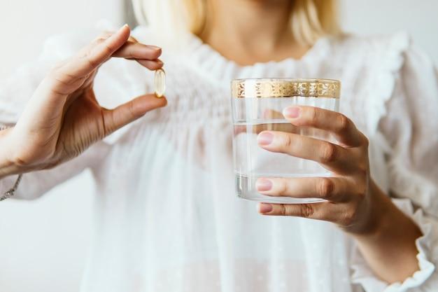Feminino mão segurando a cápsula de suplemento de óleo de peixe omega 3 e copo de água Foto Premium