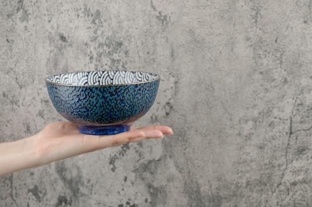 Feminino mão segurando a tigela azul vazia sobre fundo de mármore. Foto gratuita
