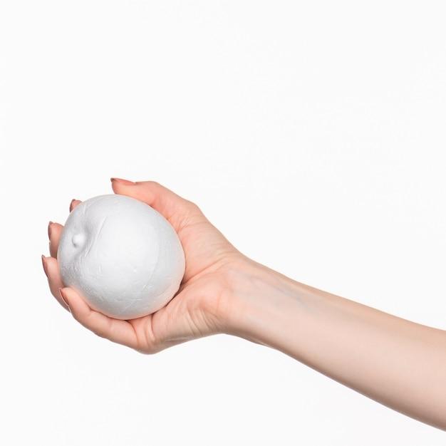 Feminino mão segurando branco oval de isopor em branco Foto gratuita