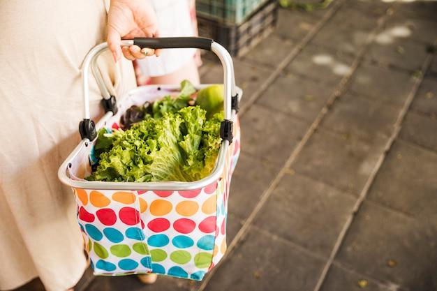 Feminino mão segurando cesta de vegetais frescos no mercado Foto gratuita