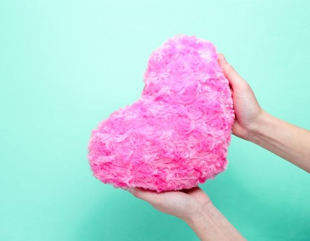 Feminino mão segurando coração rosa luxuoso sobre fundo azul. Foto Premium