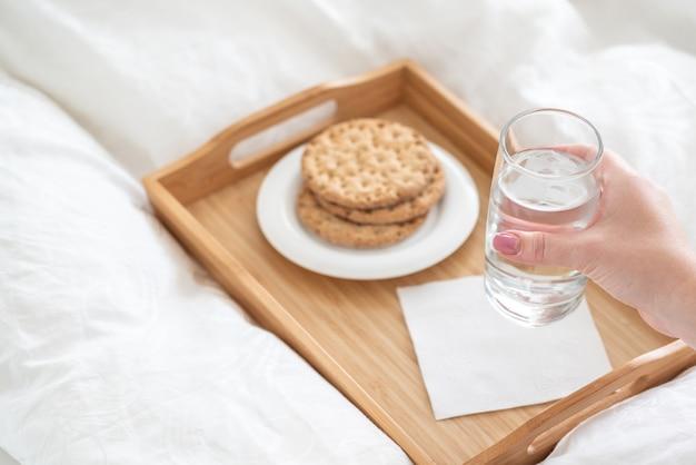 Feminino mão segurando o copo de água sobre a bandeja com biscoitos na cama Foto Premium