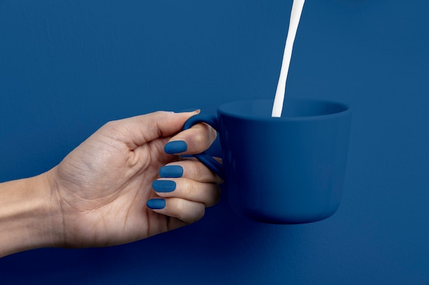Feminino mão segurando o copo de leite Foto gratuita