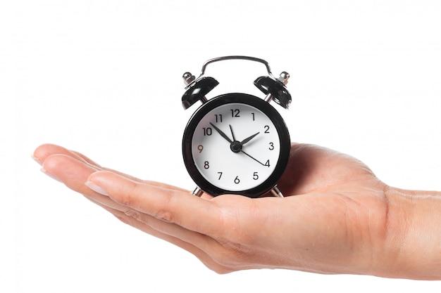 Feminino mão segurando o despertador em branco Foto Premium