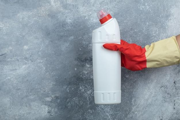 Feminino mão segurando o detergente no mármore. Foto gratuita
