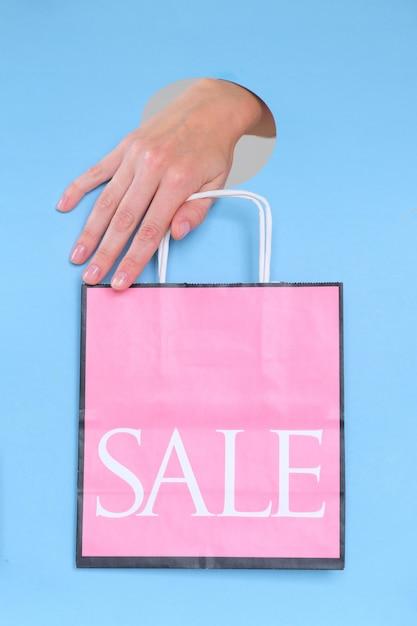 Feminino mão segurando o saco de papel rosa azul Foto Premium