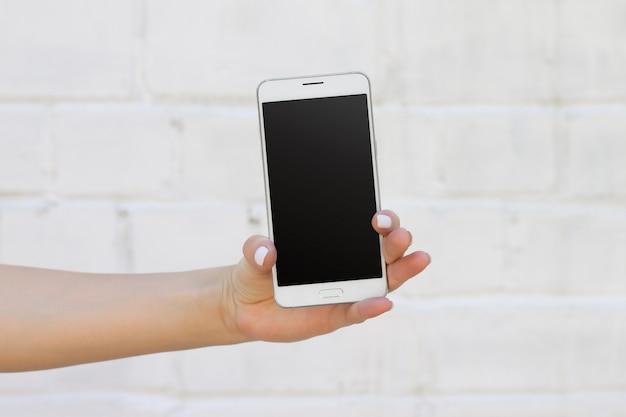 Feminino mão segurando o smartphone no fundo da parede de tijolo branco Foto Premium