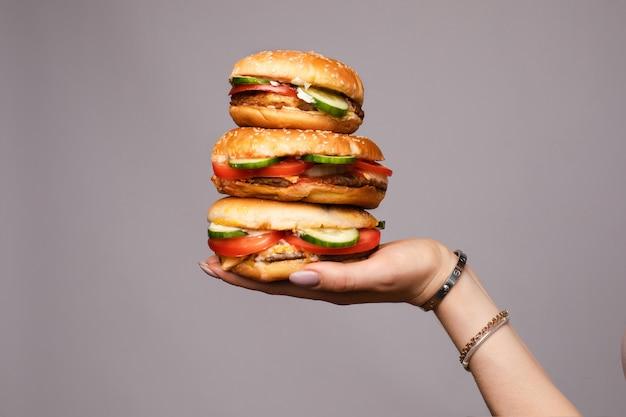 Feminino mão segurando pirâmide de três hambúrguer apetitoso isolado no estúdio cinza fundo closeup Foto Premium