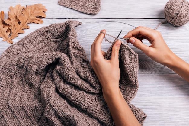 Feminino mão tricotar suéter de lã, vista superior Foto Premium