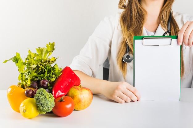 Feminino nutricionista mão segurando a área de transferência em branco com comida saudável na mesa Foto gratuita