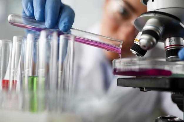 Feminino químico detém tubo de ensaio de vidro na mão closeup Foto Premium