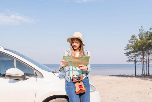 Feminino viajante inclinando-se perto do carro procurando localização no mapa Foto gratuita