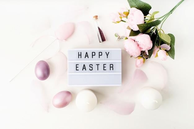 Feriado da páscoa. vista superior da caixa de luz de feliz páscoa decorada com penas e ovos em tons pastéis Foto Premium