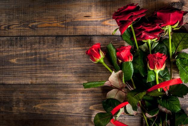 Feriado, dia dos namorados. buquê de rosas vermelhas, amarre com uma fita vermelha, com caixa de presente embrulhada. na mesa de madeira, vista superior copyspace Foto Premium