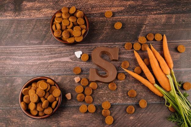 Feriado holandês de fundo sinterklaaspepernoten, carta de chocolate, doces strooigoed e cenoura para cavalo Foto Premium