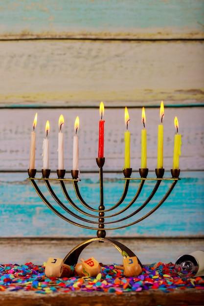 Feriado judaico hanukkah com menor candelabro tradicional e dreidels de madeira girando Foto Premium
