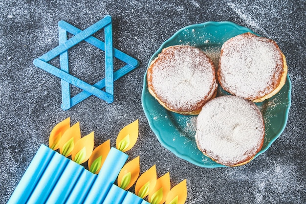Feriado judaico hanukkah e seus atributos, menorá, donuts, estrela de davi. hanukkah menor Foto Premium