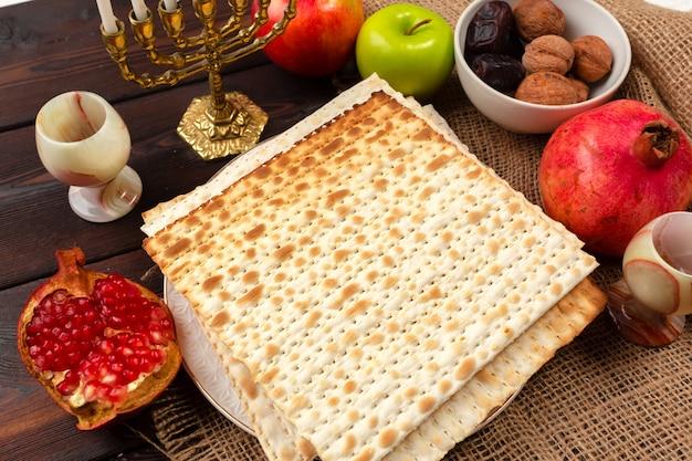 Feriado judaico mesa de páscoa com vinho, pão ázimo na madeira Foto Premium