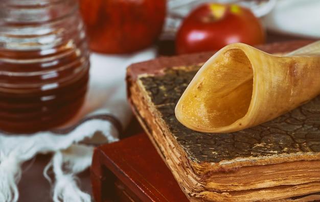 Feriado judaico rosh hashana mel e maçãs com livro de torá de romã, kipá um yamolka talit Foto Premium