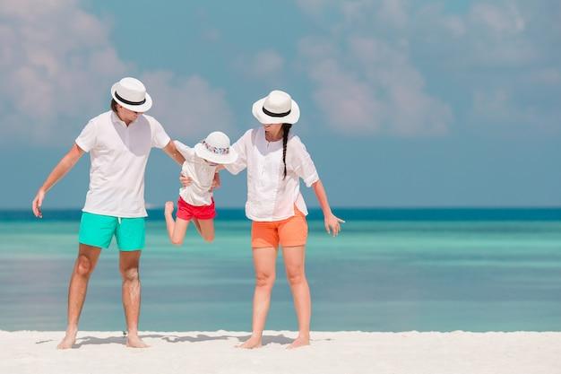 Férias de família linda feliz na praia branca Foto Premium