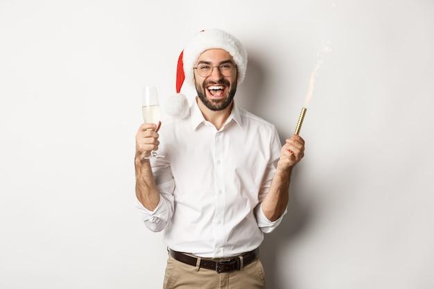 Férias de inverno e celebração. homem barbudo bonito na festa de ano novo, segurando fogo de artifício e champanhe, usando chapéu de papai noel Foto gratuita