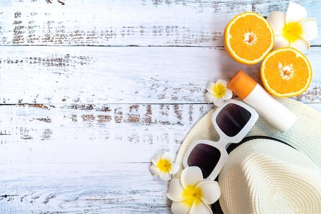 Férias de verão bonito, acessórios de praia, laranja, óculos de sol, chapéu e protetor solar Foto Premium