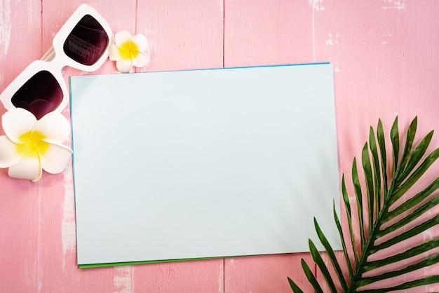 Férias de verão bonito, acessórios de praia, óculos de sol, flor e folhas de palmeira no papel Foto Premium