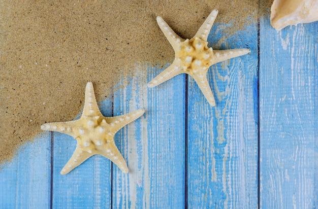 Férias de verão em placas de madeira azuis com estrela do mar na areia da praia Foto Premium