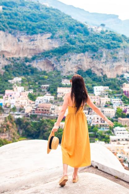 Férias de verão na itália. jovem mulher na vila de positano no fundo, costa amalfitana, itália Foto Premium
