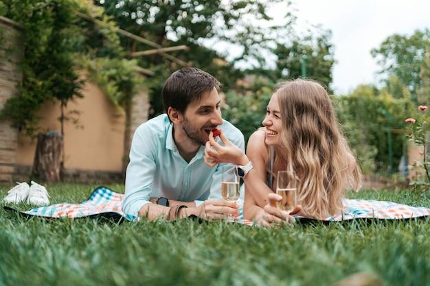 Férias de verão, pessoas, romance, homem e mulher se alimentando de morangos enquanto bebem espumantes e aproveitam o tempo juntos em casa Foto gratuita