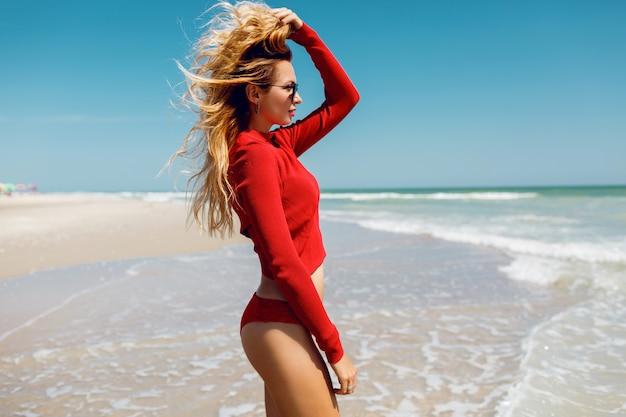 Férias e conceito de viagens. mulher loira maravilha olhando para o oceano. usando um biquíni vermelho sexy. praia vazia. ilha tropical. figura perfeita. Foto gratuita