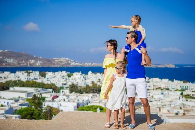 Férias em família na europa. pais e filhos a olhar para a paisagem urbana da ilha de mykonos, na grécia Foto Premium