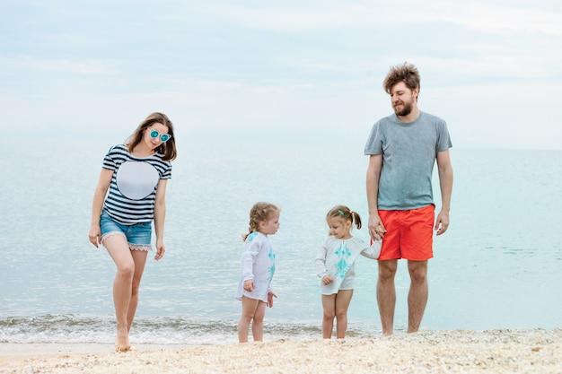 Férias em família pais e filhos na praia do mar dia de verão Foto gratuita