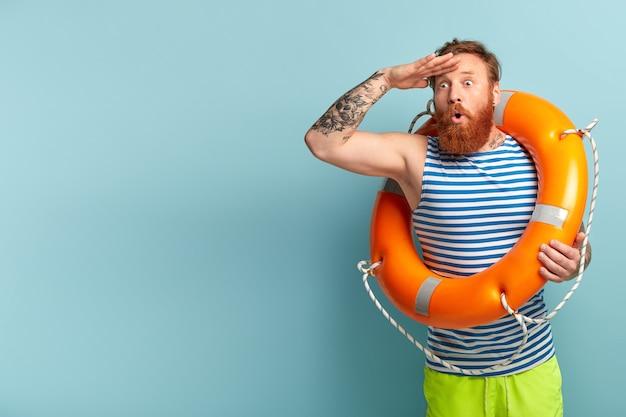 Férias no conceito de mar e resort. salva-vidas estupefato com bóia salva-vidas parece surpreendentemente distante Foto gratuita