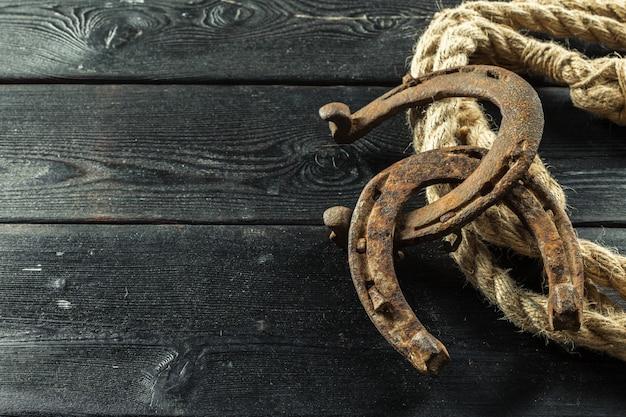 Ferradura velha e corda no fundo de madeira Foto Premium