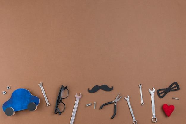 Ferramentas com bigode de papel, óculos e carro de brinquedo Foto gratuita