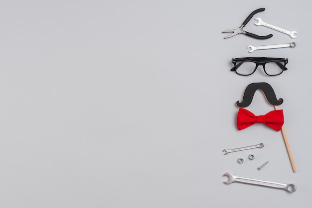 Ferramentas com bigode de papel, óculos e gravata borboleta Foto gratuita