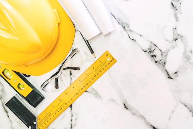 Ferramentas de construção com segurança de capacete em fundo de mármore branco Foto Premium