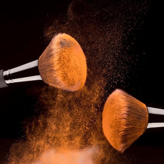Ferramentas de cosméticas e pó laranja em fundo preto Foto gratuita