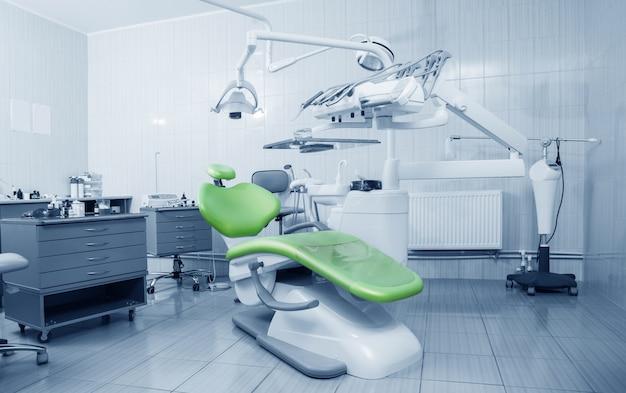 Ferramentas de dentista profissional e cadeira no consultório odontológico Foto Premium