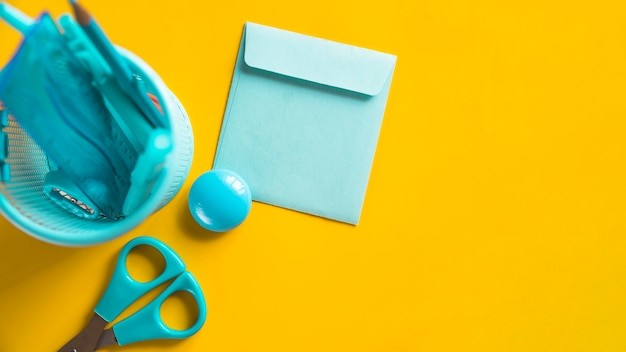 Ferramentas de escritório azul no copo na superfície amarela Foto gratuita