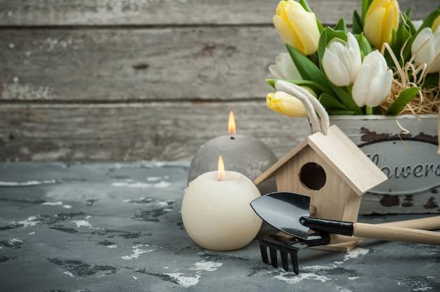 Ferramentas de jardinagem com flores e velas acesas Foto Premium