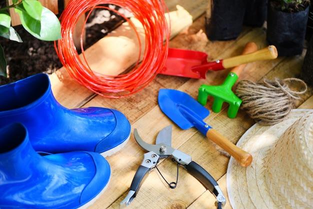 Ferramentas de jardinagem na placa de madeira com tesouras de poda corda de borracha bota de jardim espátula equipamentos Foto Premium