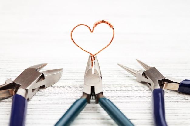 Ferramentas de joias em branco. coração feito de fio de cobre. fio revestido Foto Premium