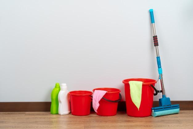 Ferramentas de limpeza para limpeza da casa no piso de madeira Foto Premium