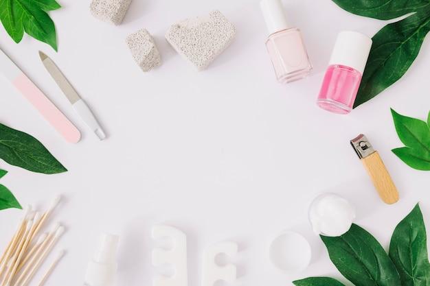 Ferramentas de manicure e produtos com folhas verdes na superfície branca Foto gratuita