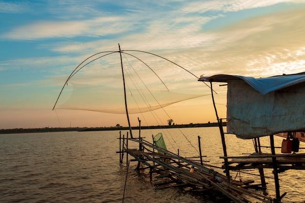 Ferramentas de pesca do pescador no lago no céu por do sol. Foto Premium