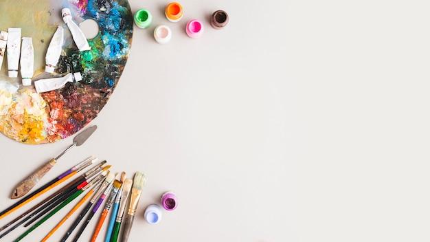 Ferramentas de pintura e pigmentos perto da paleta Foto Premium